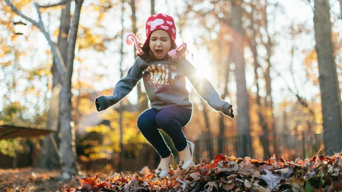 little girl doing outdoor fall activities