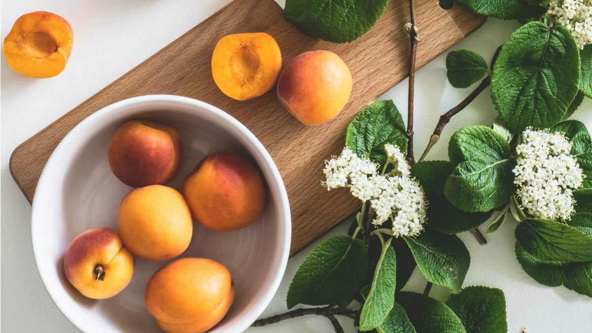 spring food peaches in a bowl with a cutting board and flowers