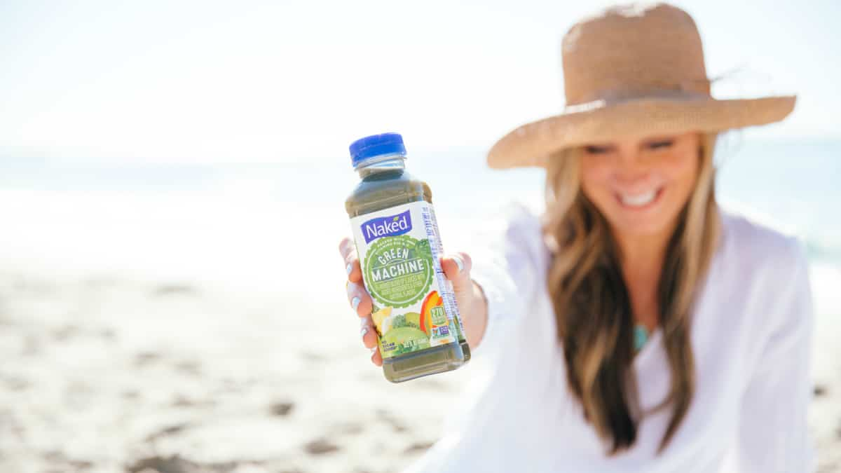 Woman holding Naked Juice Green Machine juice smoothie on a California beach