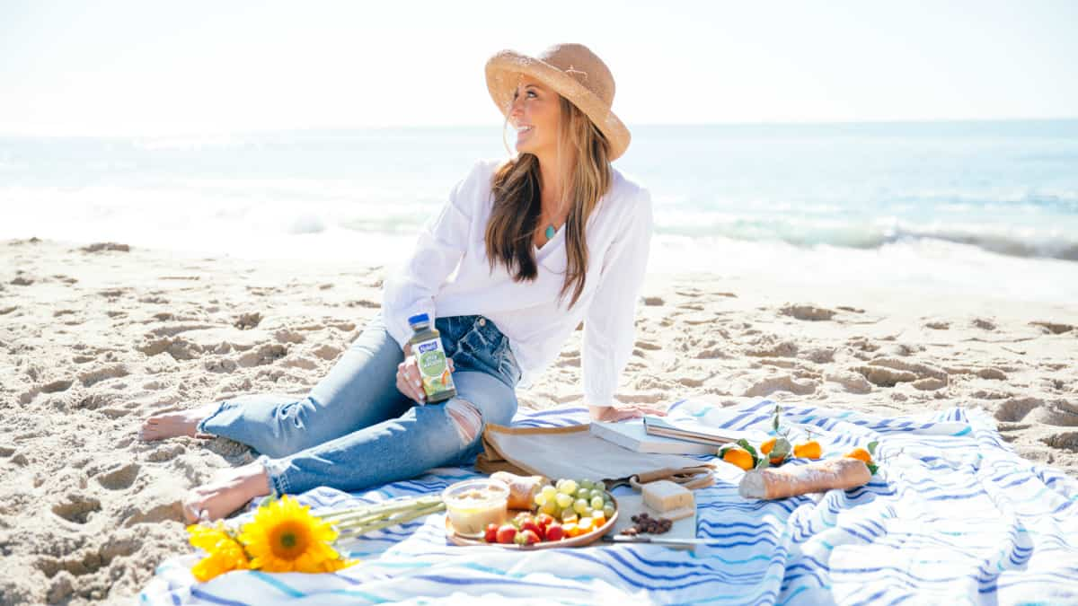 woman having picnic on the beach with Naked Juice Green Machine