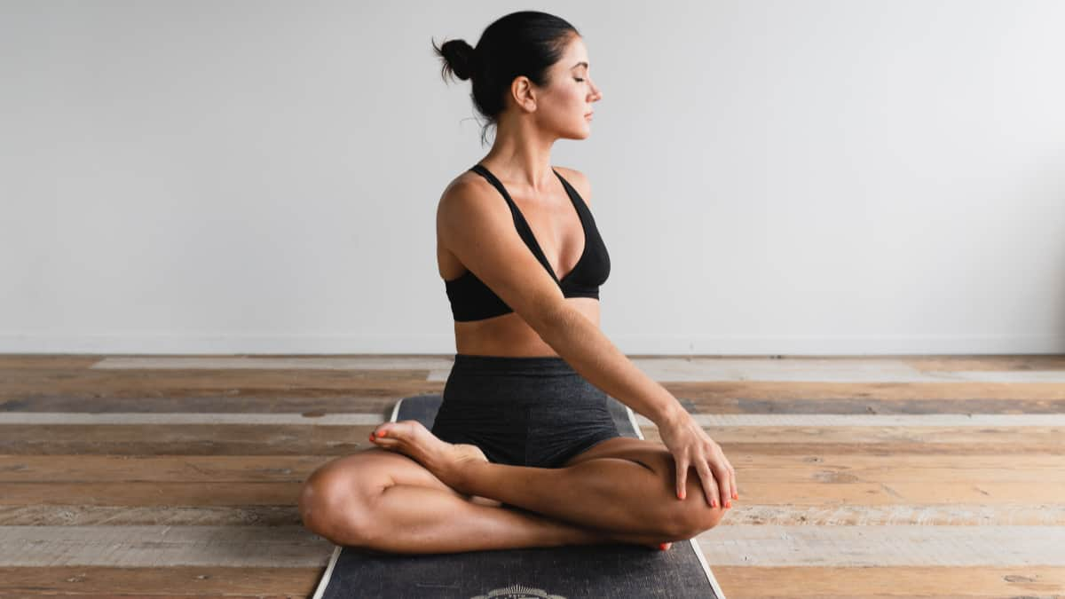 woman in yoga pose on wood floor as natural energy booster