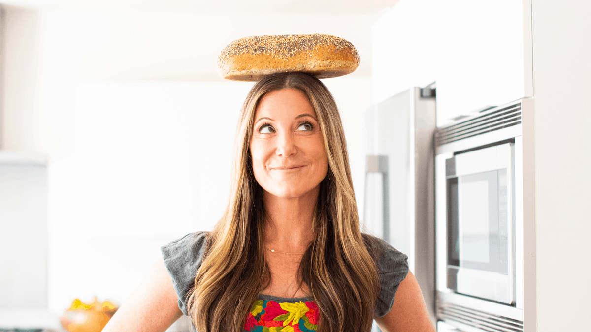 Patricia Bannan dietitian with high fiber bread balancing on her head in the kitchen