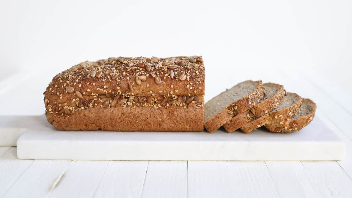 whole grain bread with slices on white cutting board