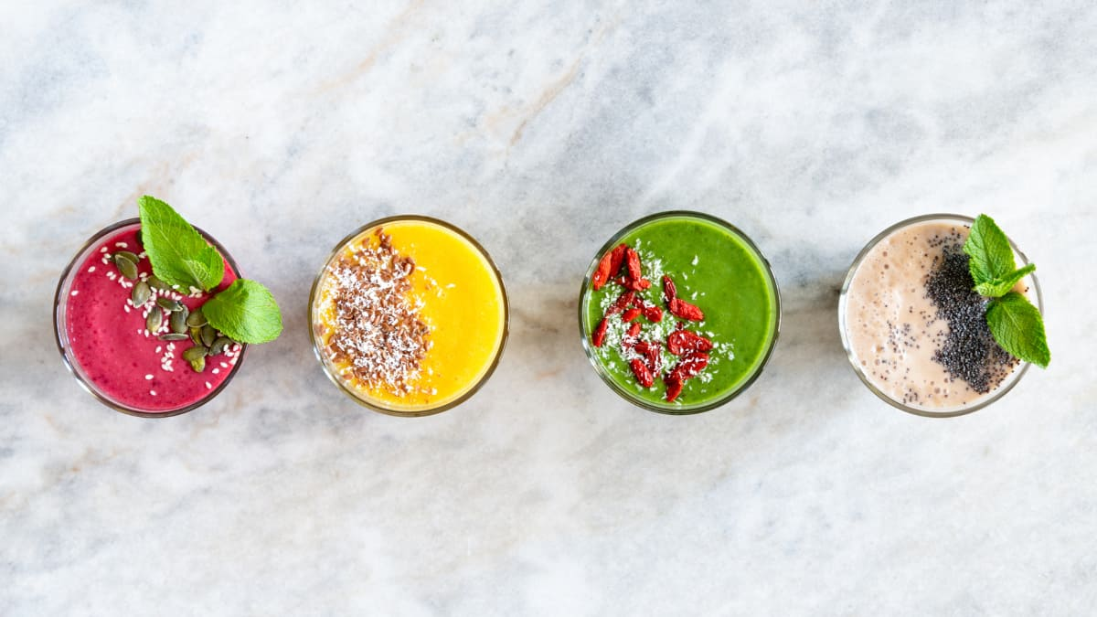 four different types of supercharged smoothies for beginners with different toppings and colors on a marble background