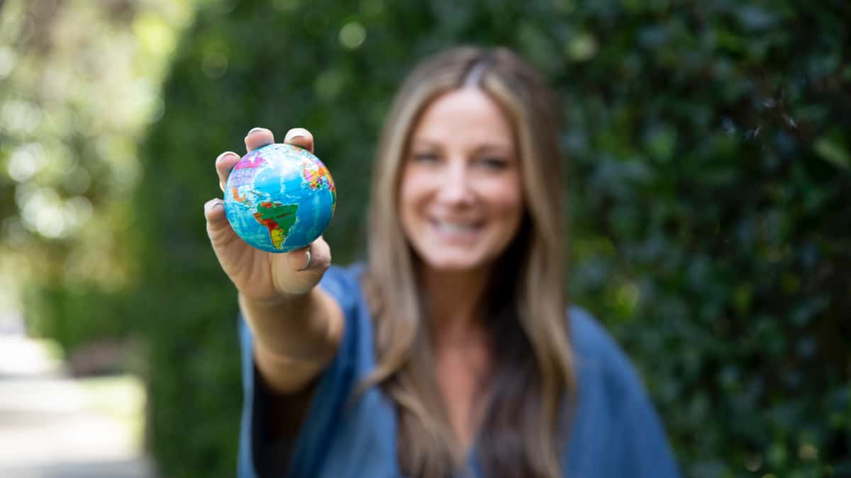 Patricia Bannan holding small earth in hand to celebrate earth month
