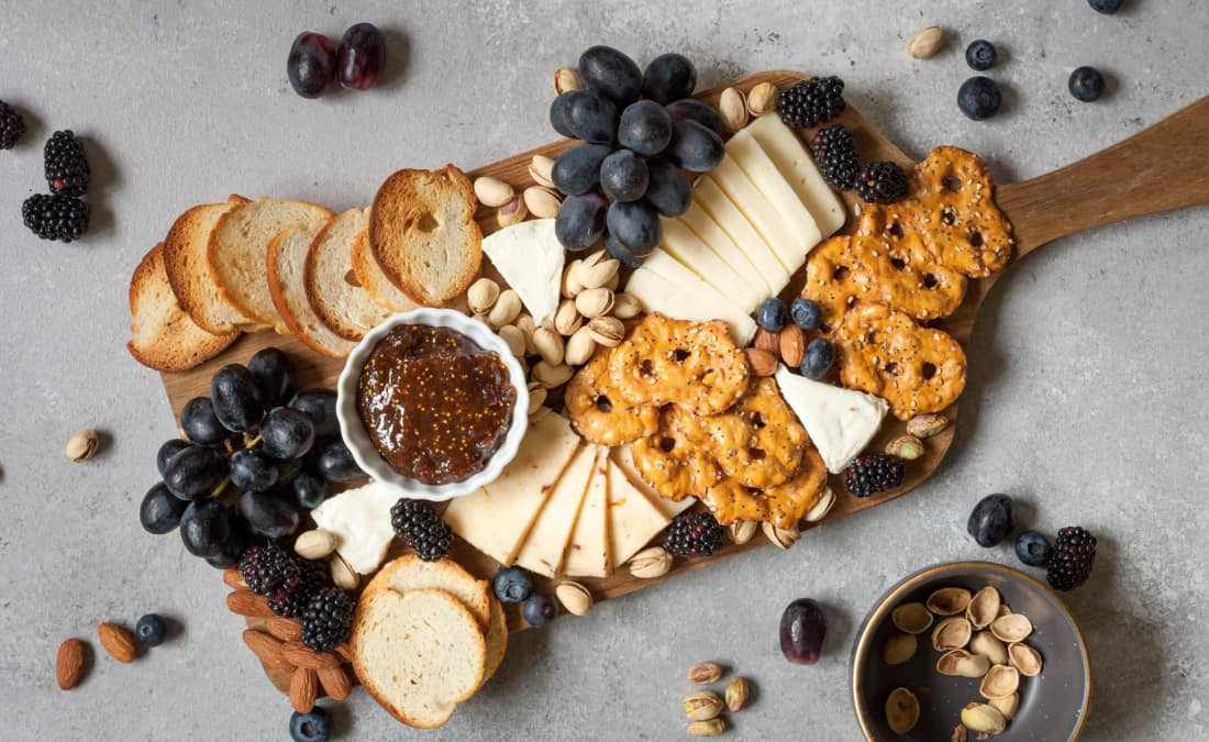 diy cheese board with different types of cheese, pretzels, crackers, fruit, and nuts