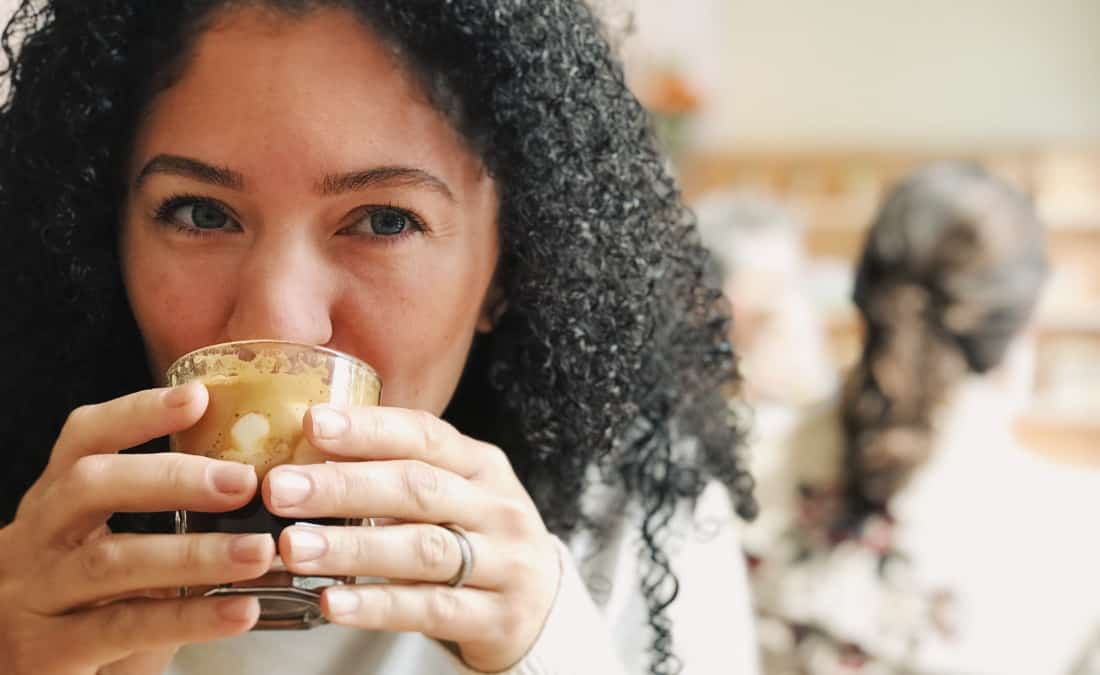 woman mindfully drinking her coffee for mindful eating exercise by smelling and tasting