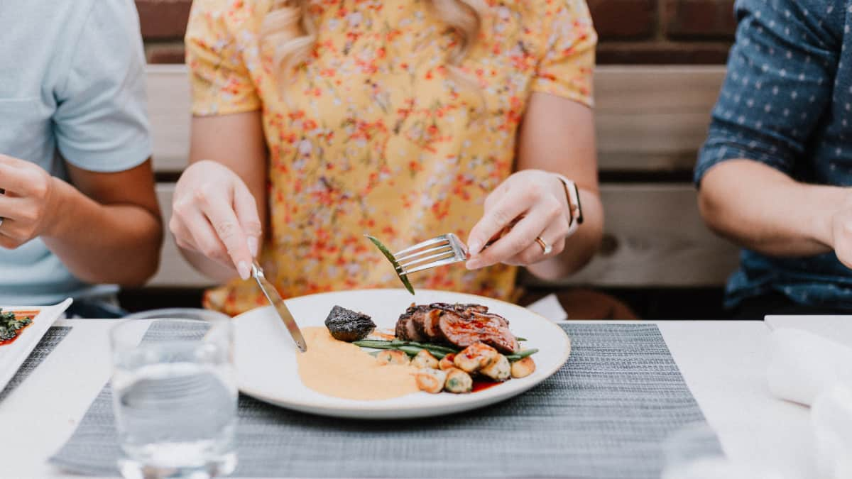 woman eating mindfully at table with small bite of food