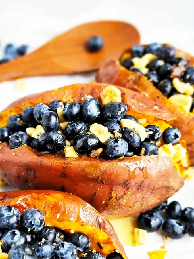 baked stuffed sweet potatoes up close with blueberries, walnuts, and cinnamon