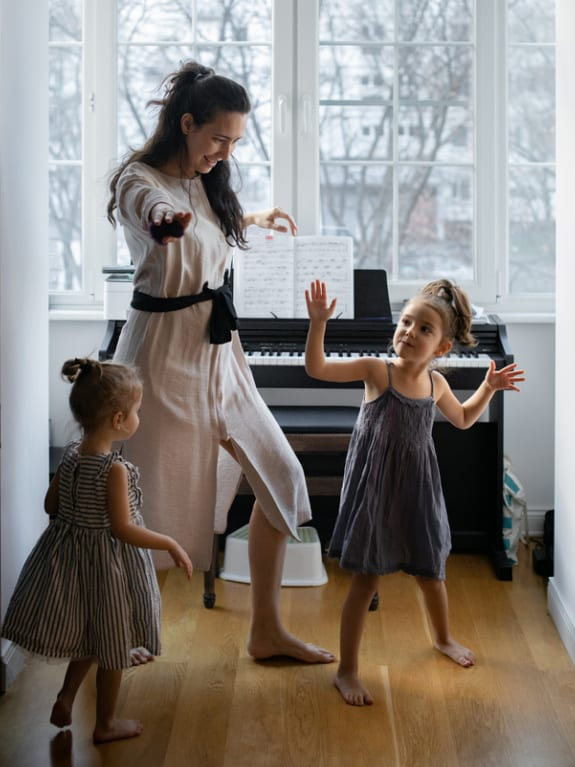 mom and daughters dancing together by piano for fun indoor activity
